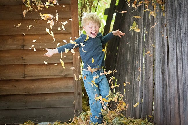 Happy boy jumping in leaves - multiple sclerosis